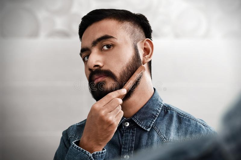 Bearded man comb his beard royalty free stock photography