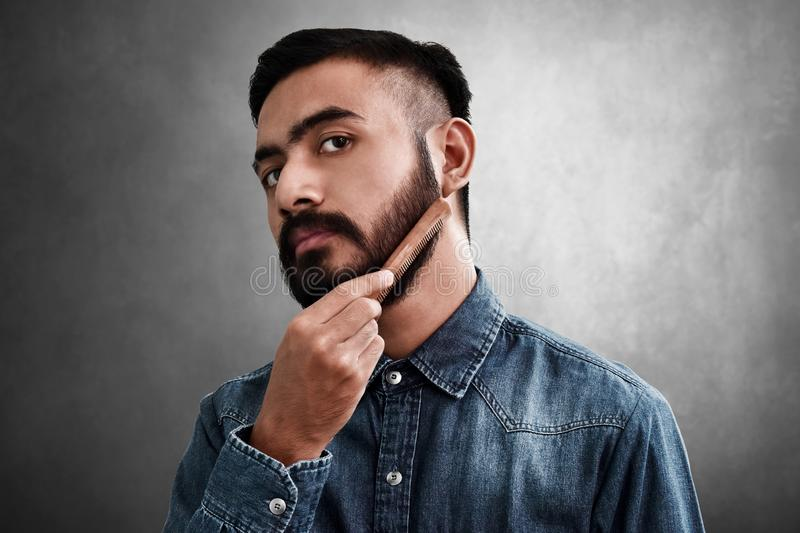 Bearded man comb his beard stock photo