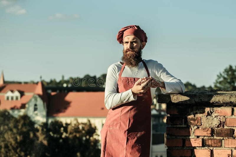 Bearded man cook chef. Handsome bearded man cook chef in uniform and red hat with long beard holds dough in hands in sunny day outdoor on city background royalty free stock photo