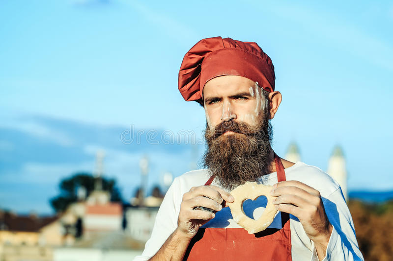 Bearded man cook chef. Handsome bearded man cook chef uniform and red hat with long beard standing with dough in shape of heart on sunny day outdoor on blue sky stock photo