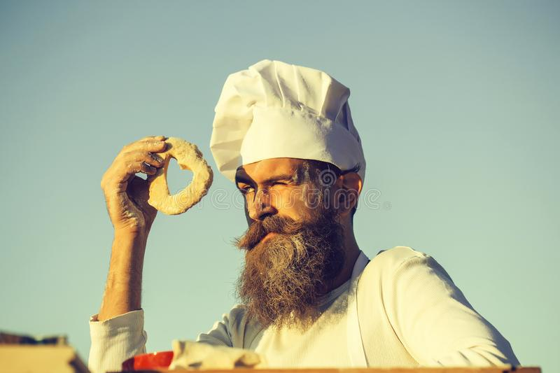 Bearded man cook chef. Handsome bearded man cook chef uniform and white hat with long beard look through dough in shape of heart on sunny day outdoor on blue sky royalty free stock photography