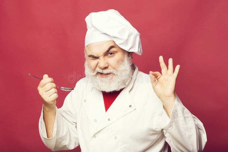 Cook with spoon. Bearded man cook in chef hat with spoon closeup in studio on pink background royalty free stock photography