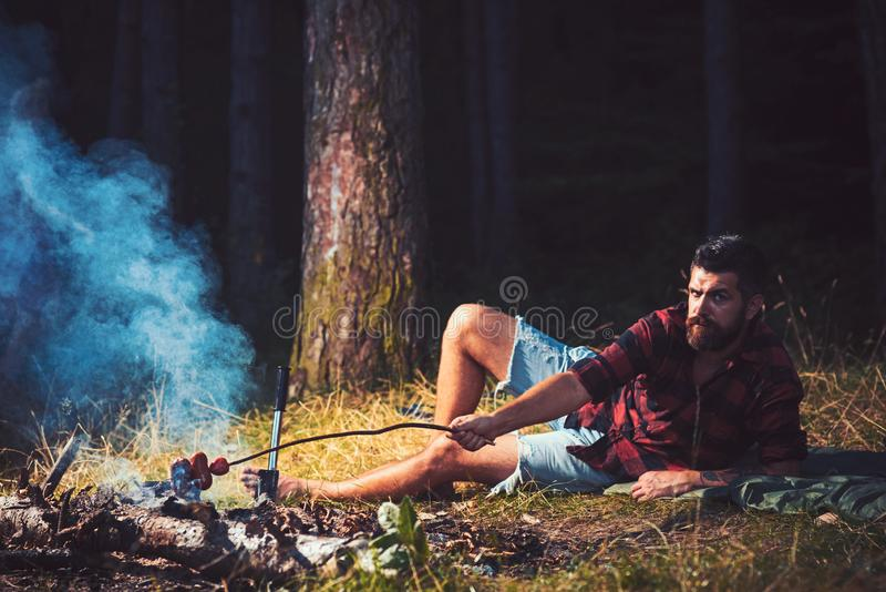 Bearded man cook food on bonfire. Hipster with beard roast sausage on fire. Man in plaid shirt relax on nature. Tourist. Enjoy camping. Summer vacation concept royalty free stock photo