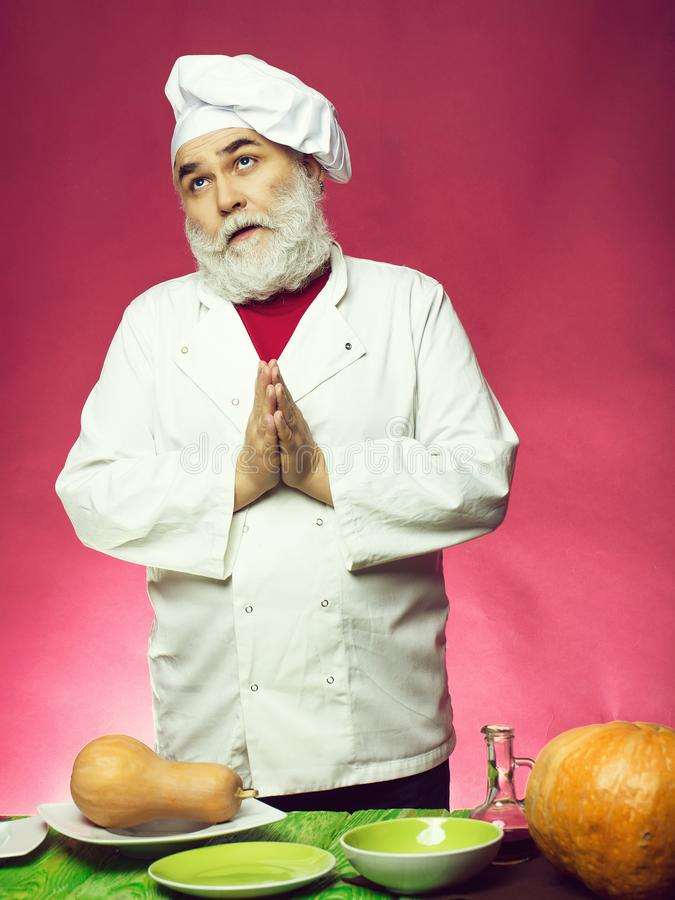 Man cook with pumpkins. Bearded man cook praying and standing near plates and dishes with pumpkins in studio on purple background stock photography