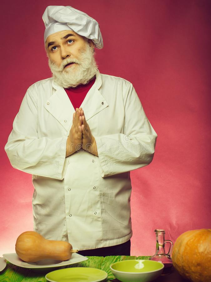 Man cook with pumpkins. Bearded man cook praying and standing near plates and dishes with pumpkins in studio on purple background royalty free stock photography