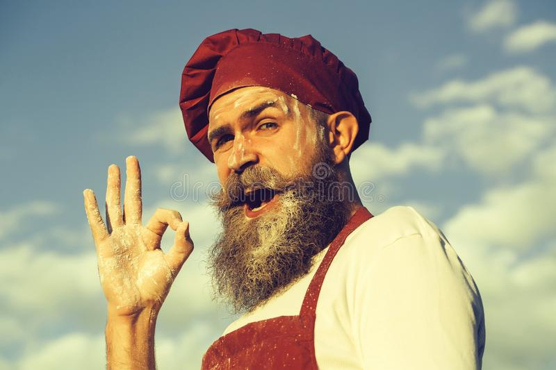 Bearded man cook in red hat stock photography