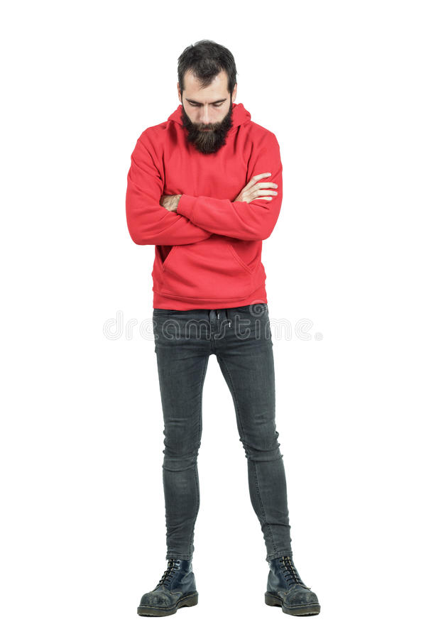 Bearded man with crossed arms in red hooded sweatshirt looking down royalty free stock images