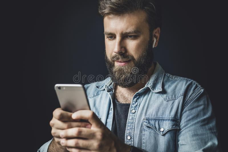 Bearded man in denim jacket using smartphone in everyday life. Guy with wireless earphones listening to music online royalty free stock image