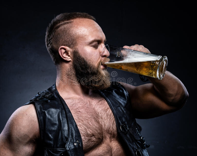 Bearded man drinking beer from a beer mug. Over grunge background stock photos