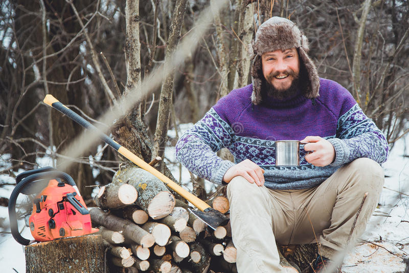Bearded man drinking tea in the forest. Bearded woodcutter at rest in winter royalty free stock photos
