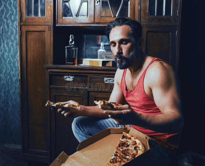 Brutal Bearded Man at Home Eating Pizza and Drinking Alcohol. stock photos