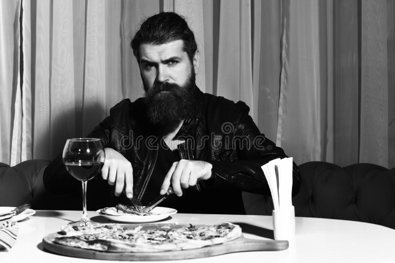 Bearded man eating pizza with knife and fork royalty free stock photo