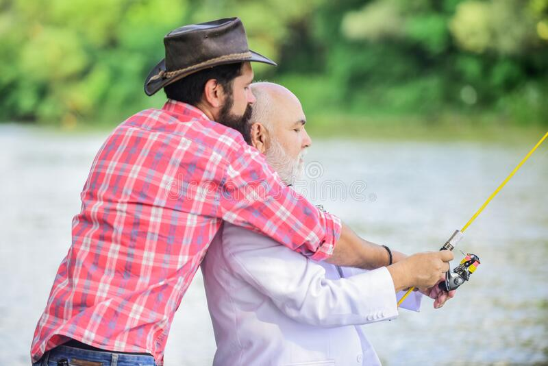 Bearded man and elegant businessman fish together. Learn to fish. Fishing skills. Men friends relaxing nature background. Bearded men and elegant businessman stock images