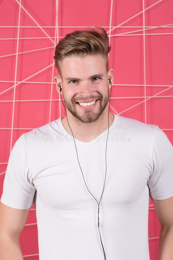 Bearded man enjoy listening music with earphones. Happy macho with audio headphone device. Media entertainment relaxation concept royalty free stock photo