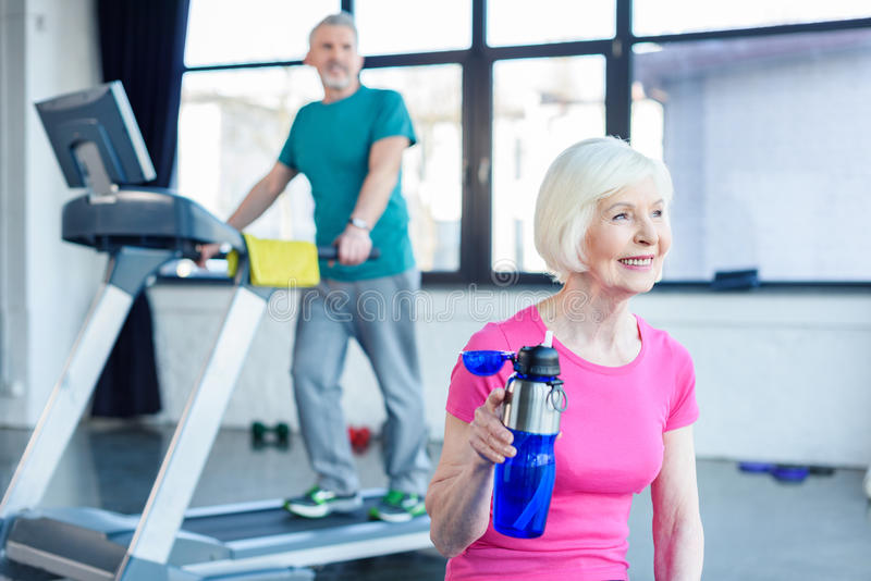 Bearded man exercising on treadmill while smiling woman drinking water stock photos