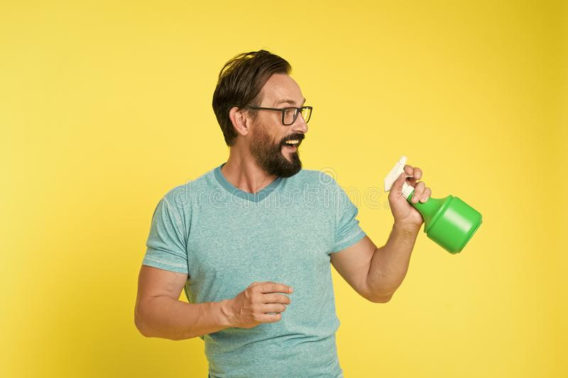 Bearded man with eyeglasses refresh sprinkling water. Man refresh with spray bottle yellow background. Time to refresh. Yourself. Heat season. Hot and thirst stock photo