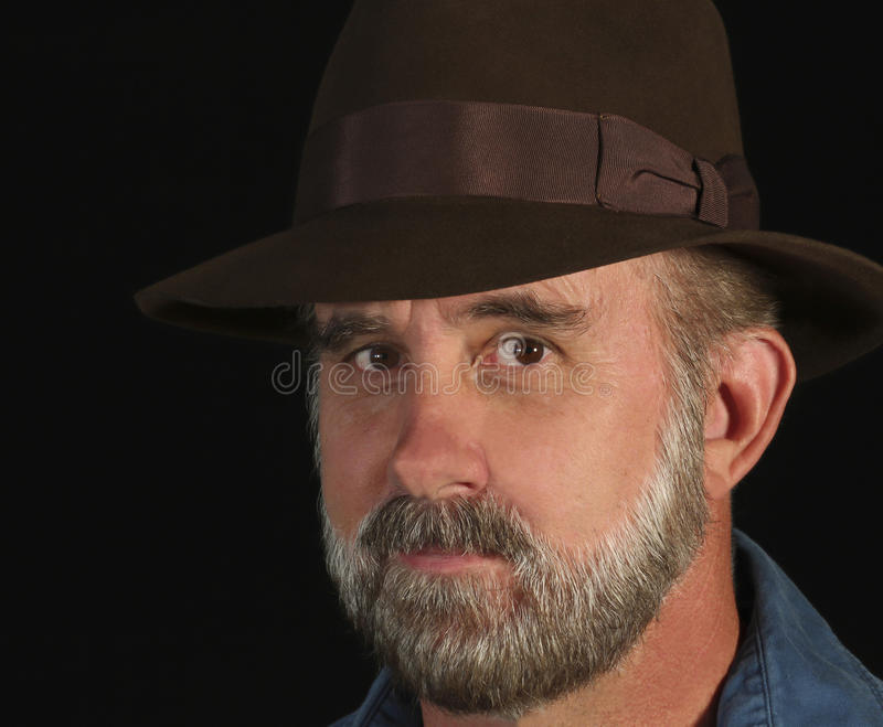 A Bearded Man in a Fedora Smiles Slightly stock photo