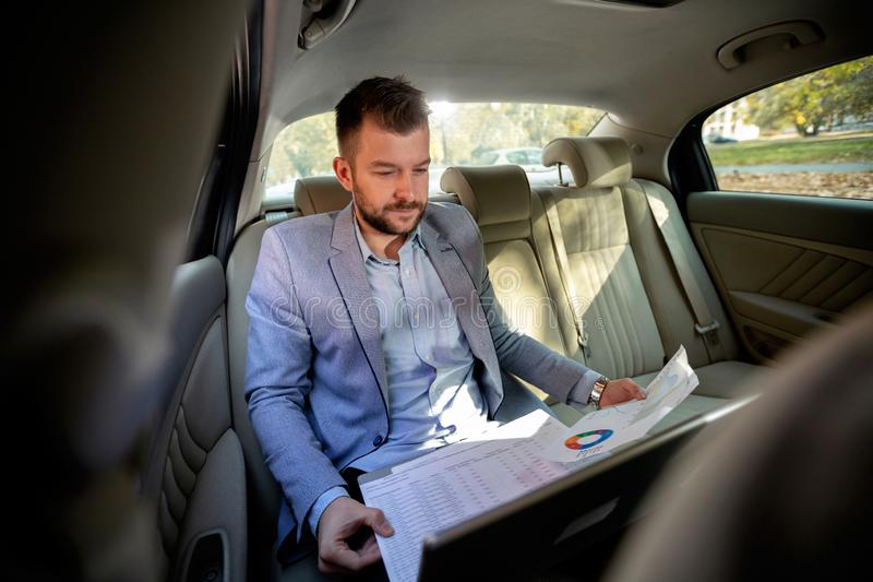 Bearded man figuring out some graphs. On his way to work stock photo