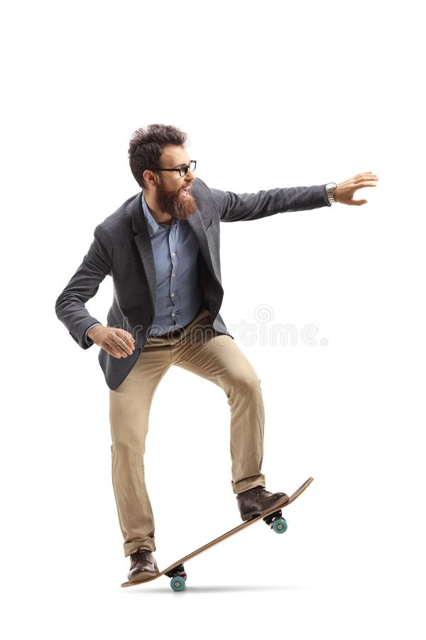 Bearded man in formal clothes riding a skateboard stock photo