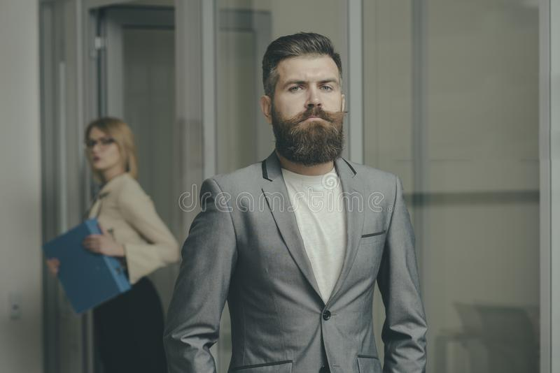Bearded man in formal suit in office. Man with beard and mustache on serious face. Confident businessman with blurred stock image