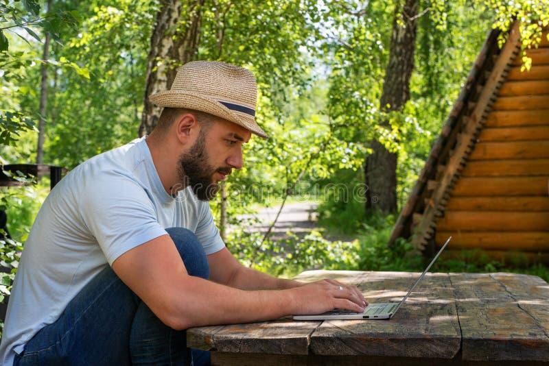 Bearded man freelancer work online on laptop. Bearded man using laptop for freelance work online outdoor. Bearded man freelancer work online on laptop. Business stock images