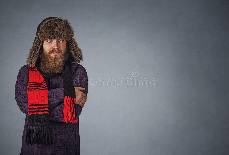 Bearded man in fur hat making cold gesture looking to the side stock photo