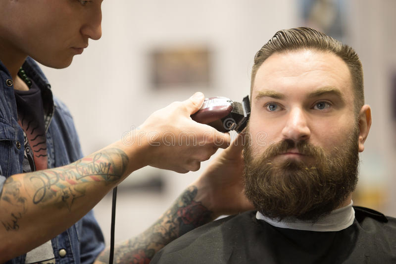 Bearded man getting haircut in barbershop royalty free stock images