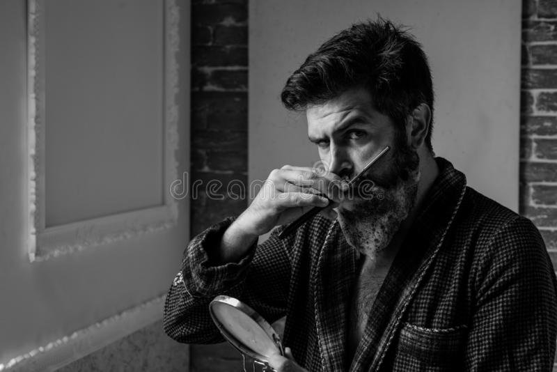 Bearded man getting haircut by hairdresser and sitting in chair at barbershop. Bearded man or hipster. Fine Cuts royalty free stock photography