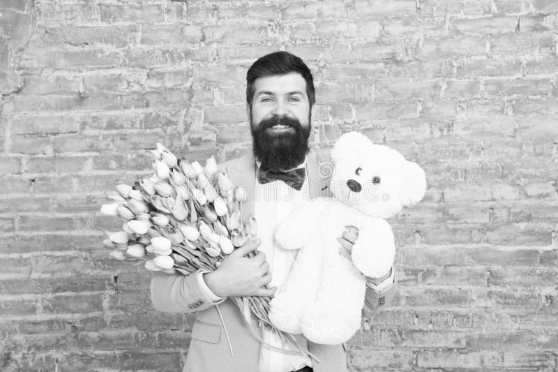 Bearded man with gifts. Womens day. Spring gift. Bearded man hipster with flowers. Love date. international holiday. March 8. Bearded man with tulip bouquet royalty free stock images