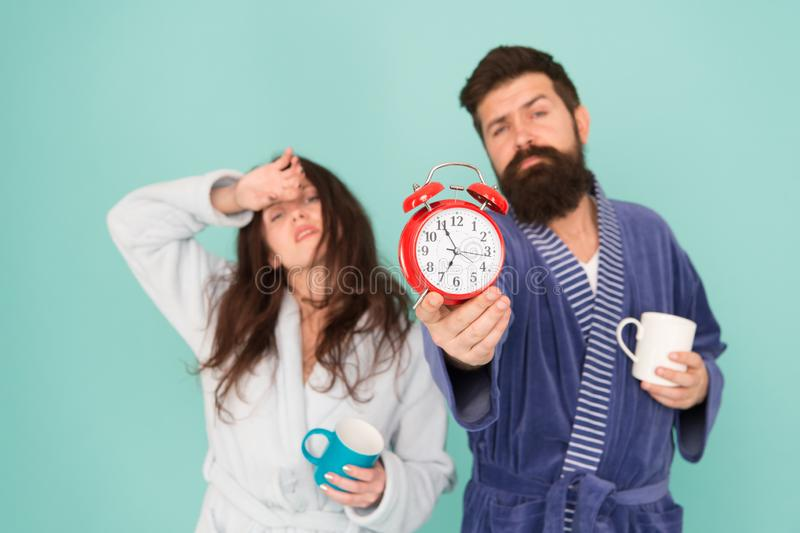 Bearded man and girl coffee cup. wake up time. family life routine. couple alarm clock. love relations. Drowsy and weak stock images