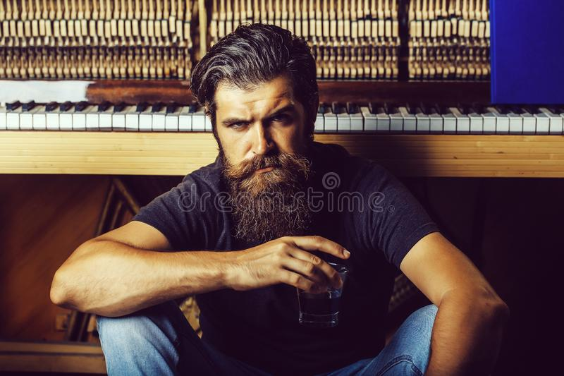 Bearded man with glass near wood piano stock photos