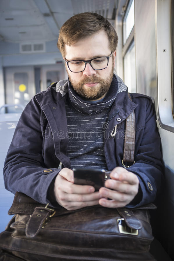 Bearded man in glasses holding a smartphone in the hands and goes to work by train stock images