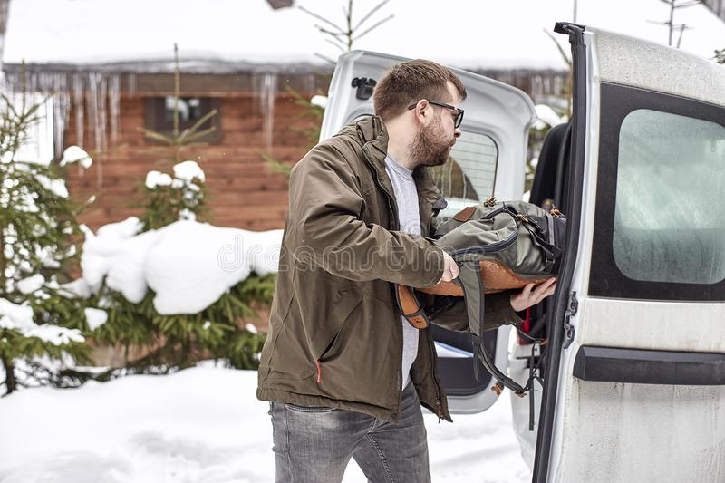 Bearded man in glasses puts things in the trunk of a car, against a background of snow-covered trees and a wooden house. Bearded man in glasses puts things in royalty free stock photography