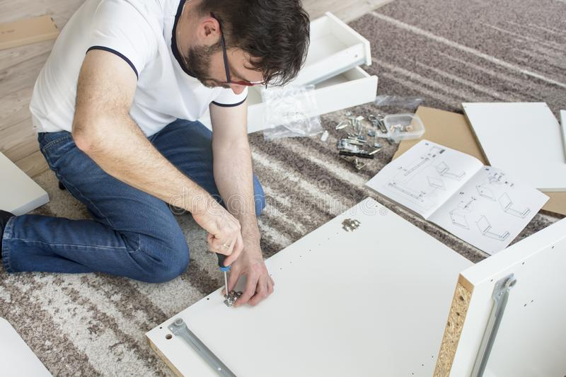 Bearded man in glasses, a white T-shirt and jeans sits on a carpet in the living room and twists furniture. He holds a screwdriv. Er and screws the hinge royalty free stock image