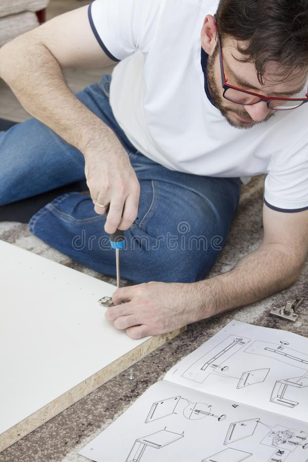 Bearded man in glasses, a white T-shirt and jeans sits on a carpet in the living room and twists furniture. He holds the hammer. A bearded man in glasses, a stock image
