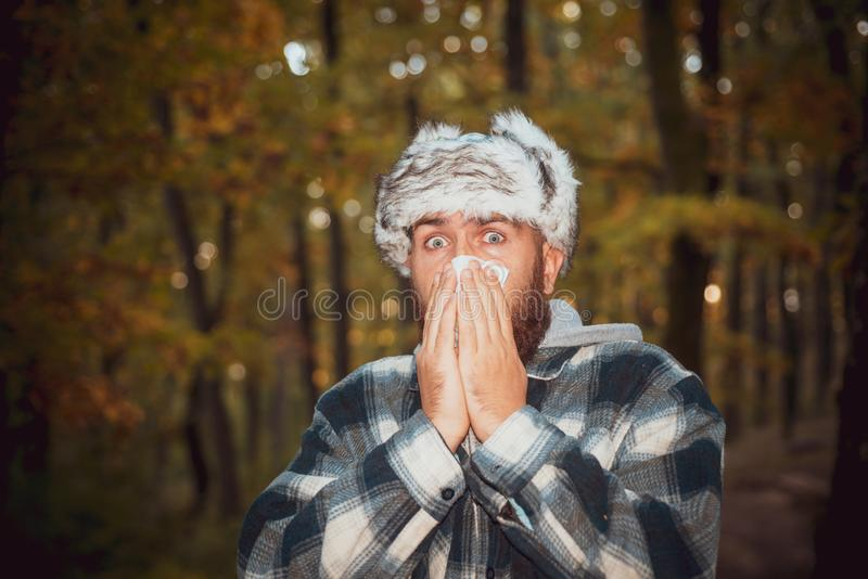 Bearded man got flu having runny nose. Sneezing boy with handkerchief in autumn park. Stop the flu epidemy. Man sneezing royalty free stock photography