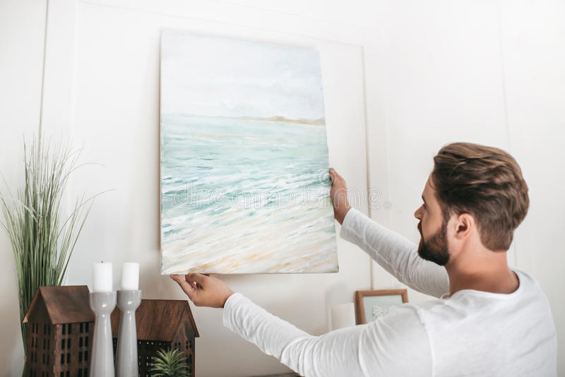 Bearded man hanging picture on wall at home stock photography