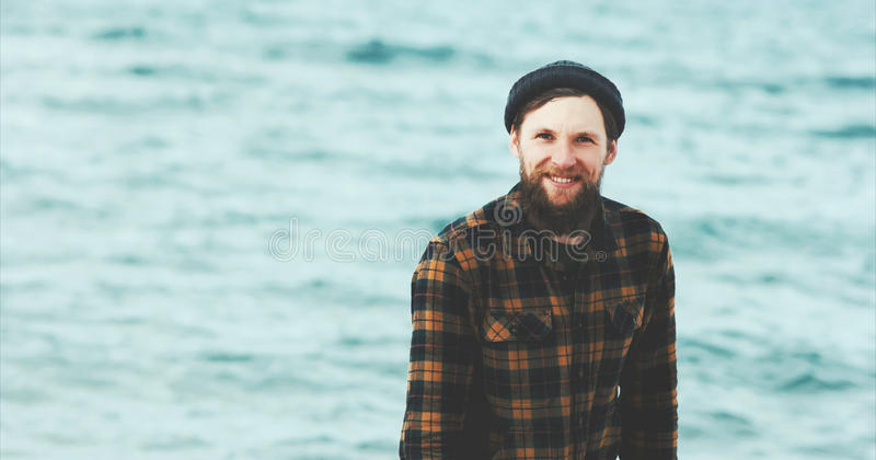 Bearded Man happy smiling walking on sea beach. Travel Fashion Lifestyle hat and cozy shirt clothing harmony with nature authentic style concept royalty free stock photos