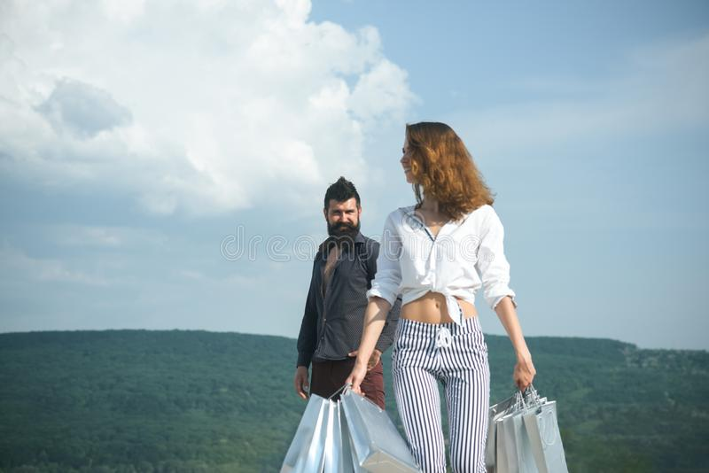 Bearded man with happy woman hold shopping bag. successful shopping. sense of freedom. couple in love. present packages royalty free stock photos