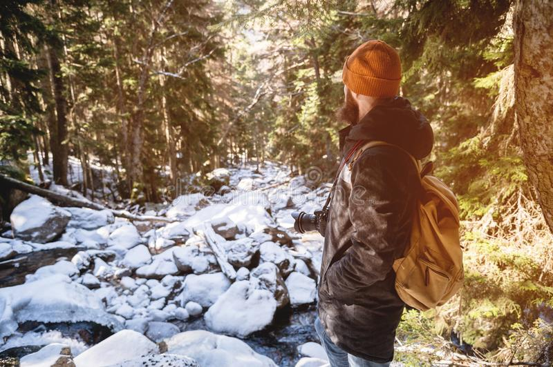 A bearded man in a hat and a backpack stands with his back in winter in a coniferous forest on the river. The concept of stock photography