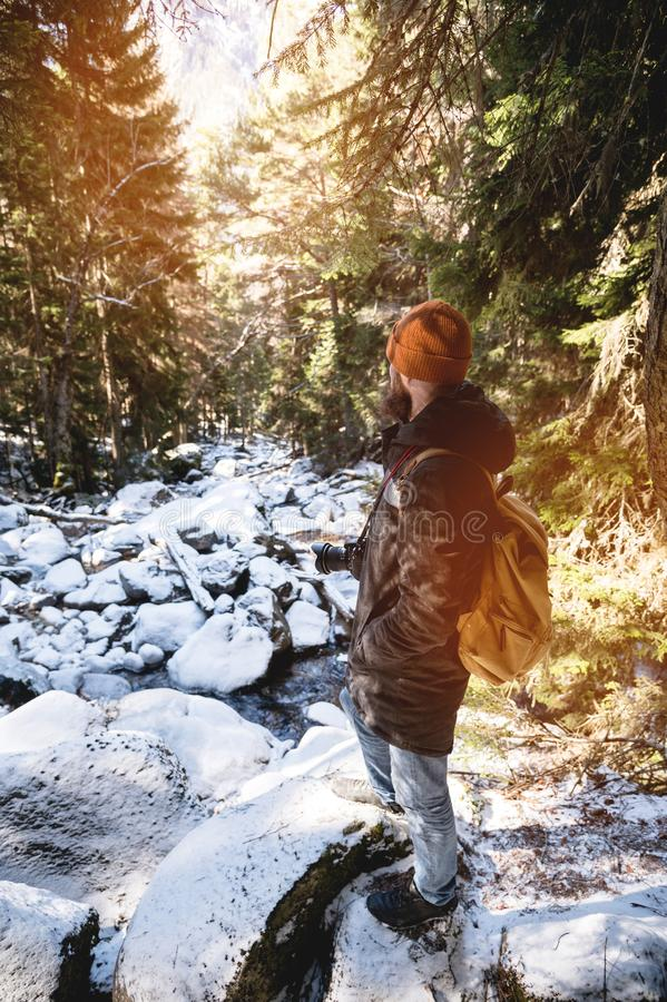 A bearded man in a hat and a backpack stands with his back in winter in a coniferous forest on the river. The concept of royalty free stock images