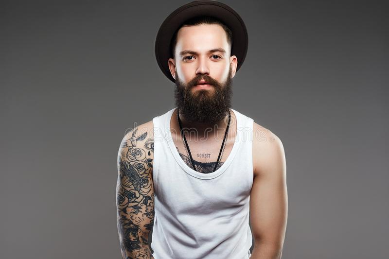 Bearded Man in Hat. hipster boy with tattoo. Handsome Bearded Man in Hat. Brutal hipster boy with tattoo royalty free stock photo