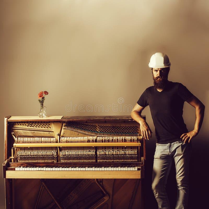 Bearded man in helmet near wood piano stock image
