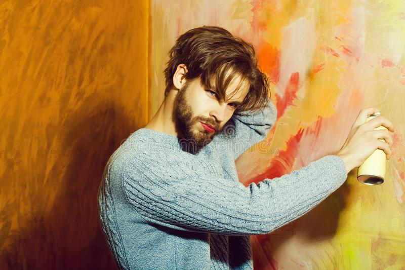 Bearded man or painter with beard with spray paint bottle royalty free stock images