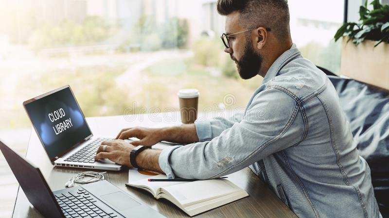 Bearded man hipster sits in cafe at table and works on laptop with inscription on monitor- cloud library. Student learning online stock images