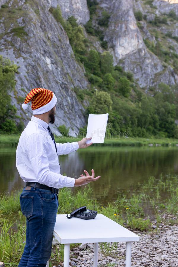 Bearded man, hipster in a white shirt and santa hat holds a blank sheet of paper in hand. Reads a speech. Against the backdrop of a mountain river on a summer stock photo