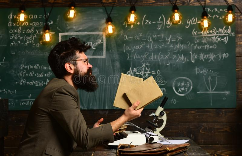 Bearded man hold books in university. Scientist research with microscope. Man with beard and mustache on chalkboard royalty free stock images
