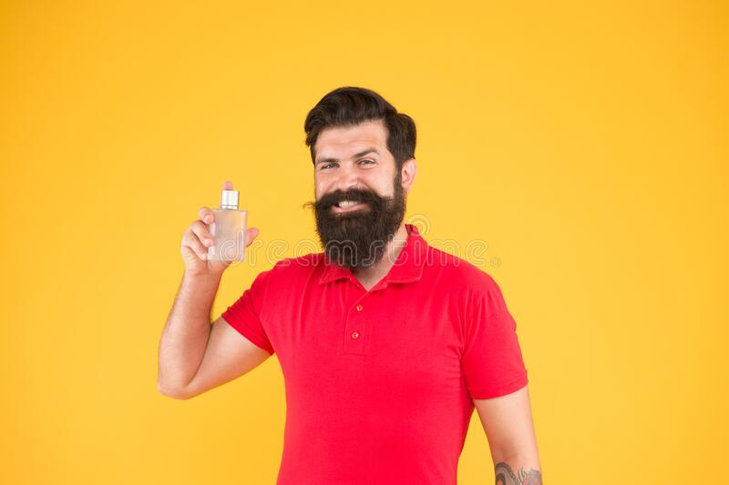 Bearded man hold perfume bottle. perfect aroma for real men. brutal hipster choose smell. mature man recommended stock photo