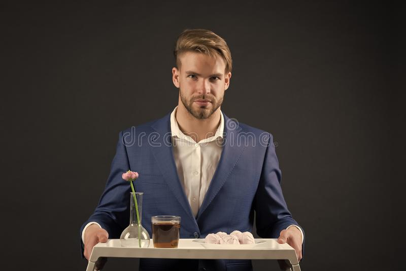 Bearded man hold tray with flower. Macho serve dessert food and drink. Waiter in formal suit. Service and restaurant royalty free stock photography