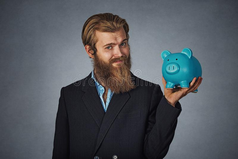 Bearded man holding a piggy bank against a gray grunge background stock photography